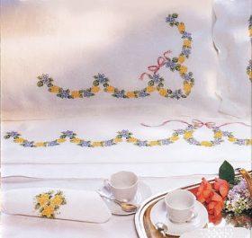 Sbocciano tenere corolle sul lenzuolo della sposa ricamato a puntocroce.